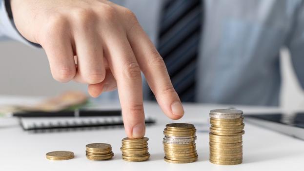 dois dedos caminhando em cima de uma pilha crescente de moedas