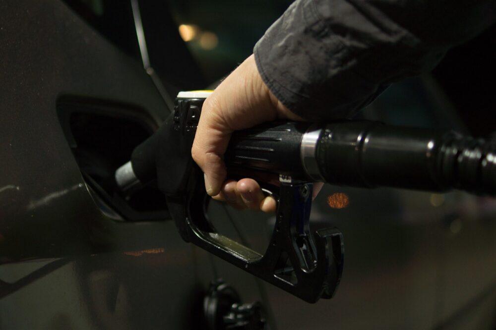 imagem ampliada da mão de alguém segurando objeto de abastecer carro dentro do tanque do carro